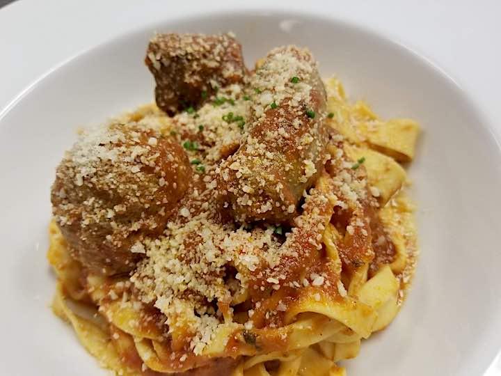 Italian gravy on pasta with Italian sausage on top.